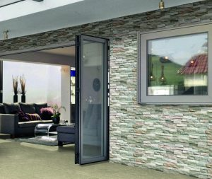 Bi fold doors opening onto patio area. Same flooring running from the inside area to the exterior.